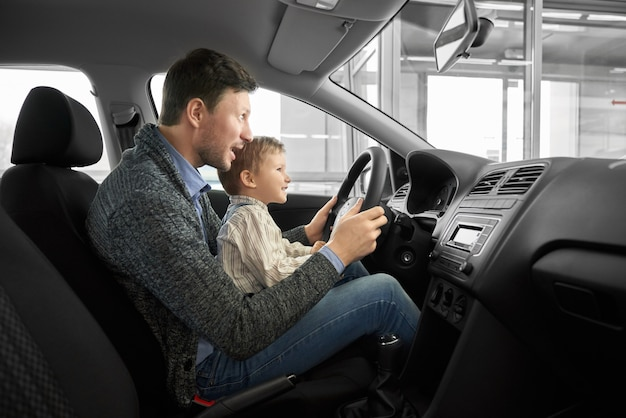 Divertido papá e hijo sentados en el asiento de los conductores en auto nuevo