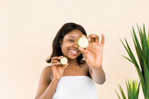 Divertido retrato de la bella modelo africana negra con piel suave que sostiene una rodaja de pepino en su ojo, rejuvenece el tratamiento del régimen de cuidado de la piel, concepto de belleza facial