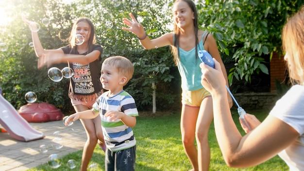 Divertido retrato de familia joven alegre feliz soplando y cathcing pompas de jabón en el jardín del patio de la casa