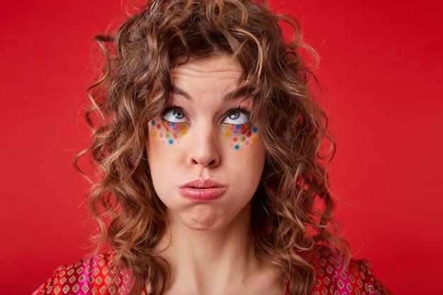 Divertido retrato de mujer joven y bonita con cabello rizado y maquillaje festivo mirando hacia arriba y soplando en su cabello, burlándose mientras posa, vistiendo la parte superior estampada abigarrada
