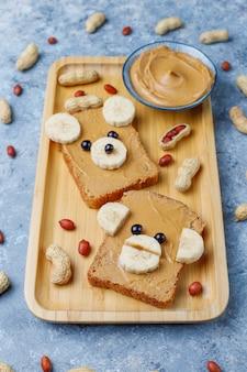 Divertido sandwich de cara de oso y mono con mantequilla de maní, plátano y grosella negra, maní, vista superior