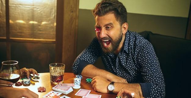 Divertidos amigos masculinos y femeninos sentados en la mesa de madera. hombres y mujeres jugando al juego de cartas. manos con primer plano de alcohol.