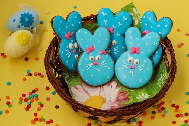 Divertidos conejos azules de pascua, galletas de jengibre pintadas caseras en esmalte en una cesta de mimbre sobre un fondo amarillo