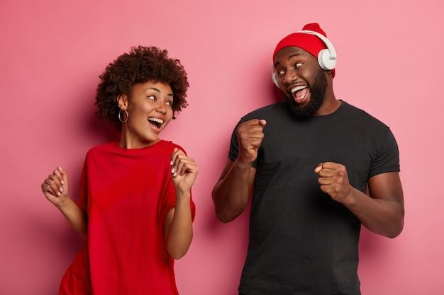 Divertidos hombres y mujeres de piel oscura disfrutan escuchando la lista de canciones favoritas, bailan con el ritmo de la música, usan auriculares modernos