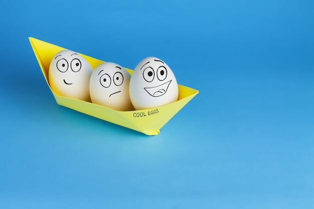 Divertidos huevos con caras dibujadas flotan en el barco. tres huevos blancos en un barco de papel amarillo sobre una mesa azul. concepto de pascua y viajes.