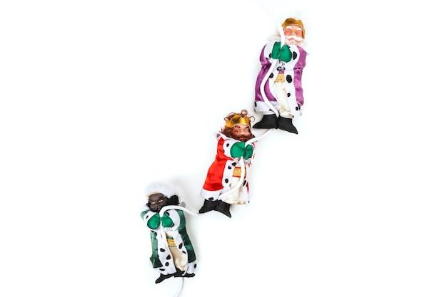 Divertidos muñecos navideños de tres reyes magos colgando de una cuerda