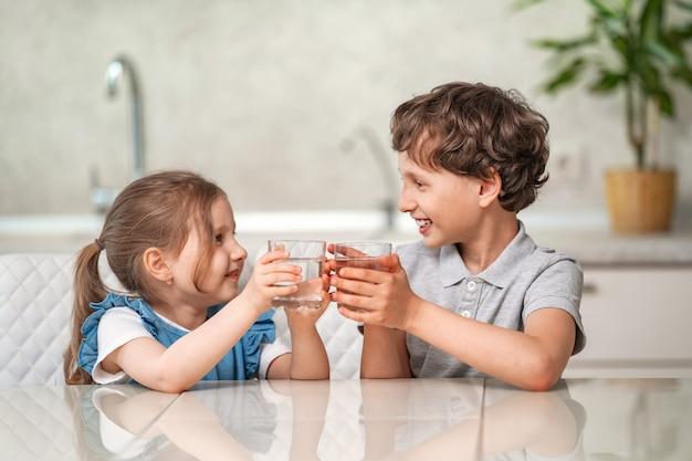 Divertidos niños beben agua en la cocina en casa