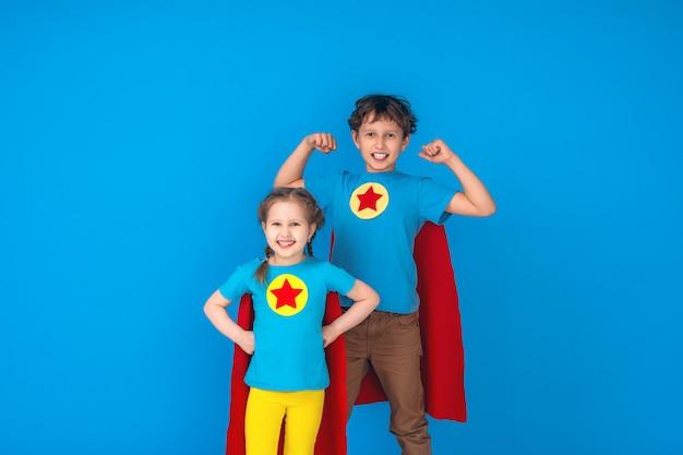 Divertidos niños superhéroe poder en impermeables rojos y máscara.