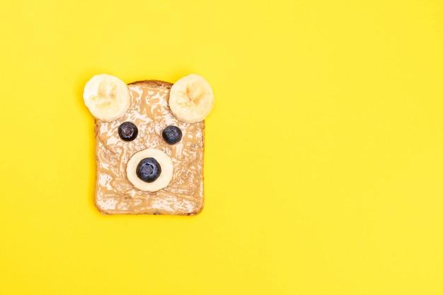 Divertidos niños tostadas de desayuno con mantequilla de maní en forma de oso con arándanos y plátano. vista superior, espacio de copia