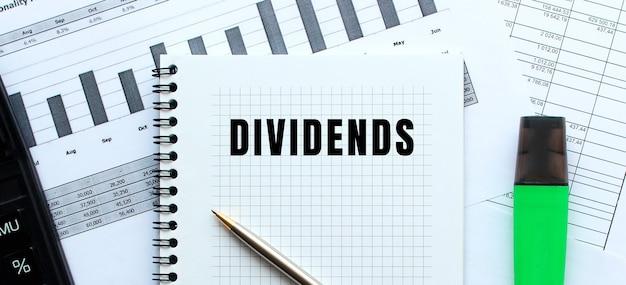 Dividendos de texto en la página de un bloc de notas sobre gráficos financieros