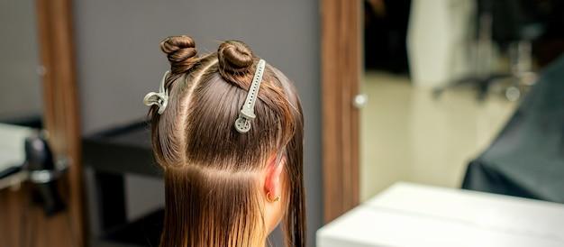 Dividió el cabello de las mujeres en secciones con clips en la barbería.