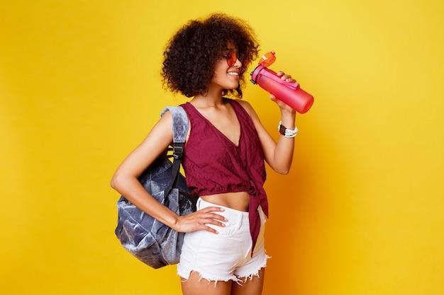 Diviértase a la hembra negra que se coloca sobre fondo amarillo y que sostiene la botella rosada de agua. con ropa de verano elegante y mochila.