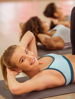 Diviértase a las muchachas que sonríen mientras que trabaja mintiendo en la estera de la yoga.