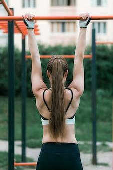 Diviértase a la mujer morena joven en la ropa de deportes tirada en la barra al aire libre.