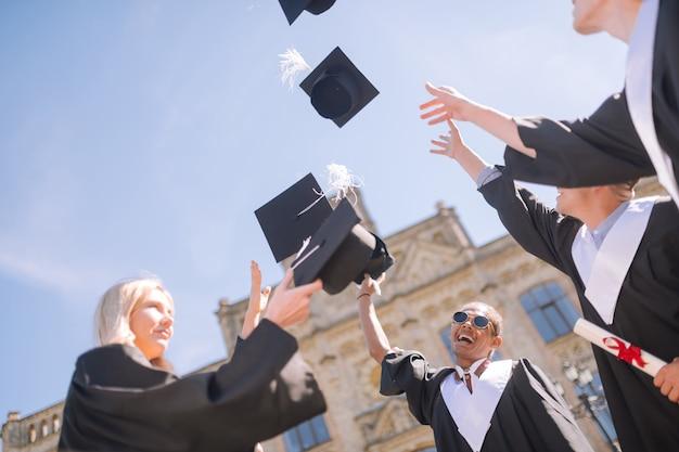 Divirtiéndonos juntos. estudiantes graduados alegres de pie en el patio de la universidad cogiendo sus gorras de maestría y riendo.