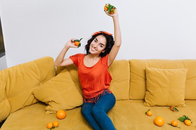 Divirtiéndose en casa de una mujer joven y bonita emocionada increíble con cabello rizado de corte morena sonriendo en el sofá naranja entre mandarinas en la sala de estar.