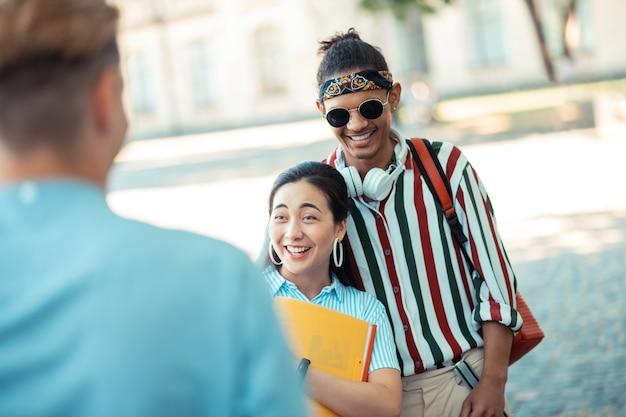 Divirtiéndose mucho. pareja joven alegre de pie cerca uno del otro frente a sus amigos y riendo en el patio de la universidad.