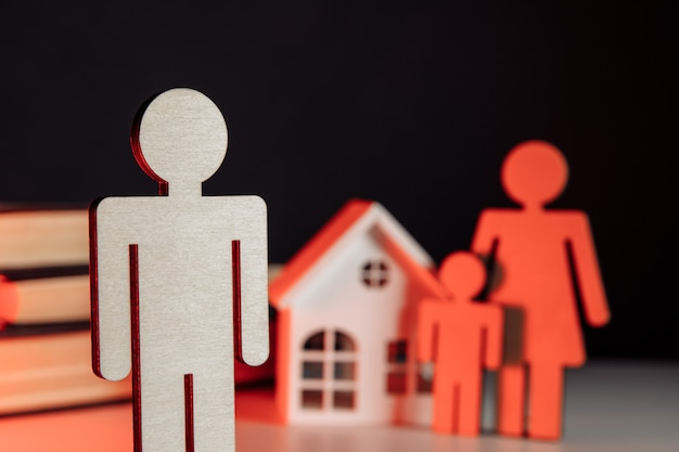 Divorcio y divide modelos conceptuales de familia con niño y primer plano de la casa