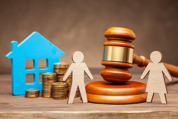Divorcio por ley. división de bienes después de un divorcio. la esposa está tratando de demandar a su esposo por propiedades según la ley. un hombre con casa y dinero, y una mujer con un martillo de juez.