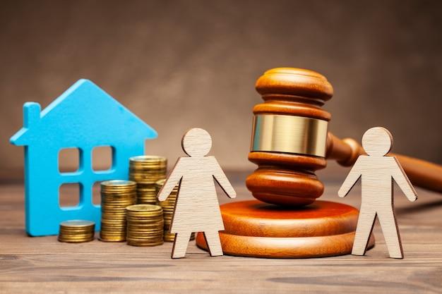 Divorcio por ley. división de bienes después de un divorcio. el esposo está tratando de demandar a su esposa por propiedades según la ley. una mujer con casa y dinero, y un hombre con un martillo de juez.