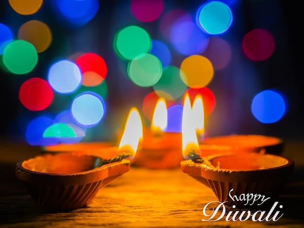Diwali feliz - las lámparas de diya se encendieron y las flores con el fondo del bokeh durante la celebración del diwali.
