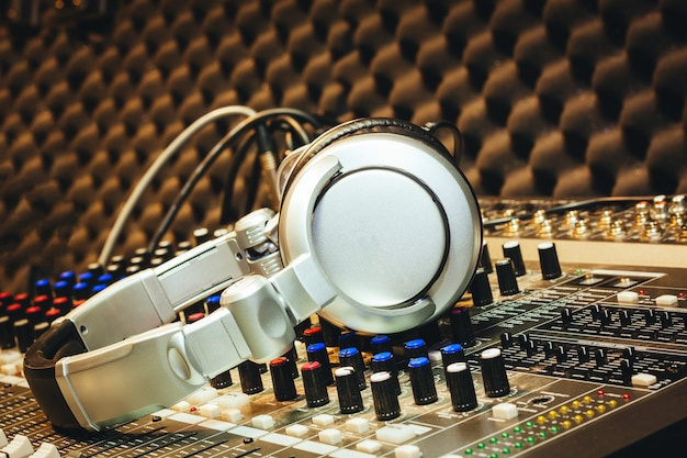 Dj accesorios de herramientas auriculares en tablero mezclador de sonido en el estudio de grabación casera.