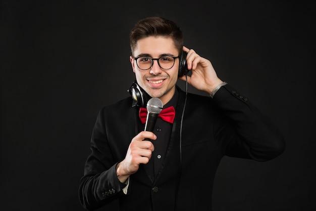 Dj con auriculares y micrófono sobre un fondo negro