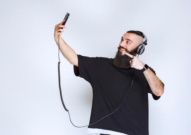 Dj con barba con auriculares abriendo la cámara del teléfono inteligente y tomando su selfie.