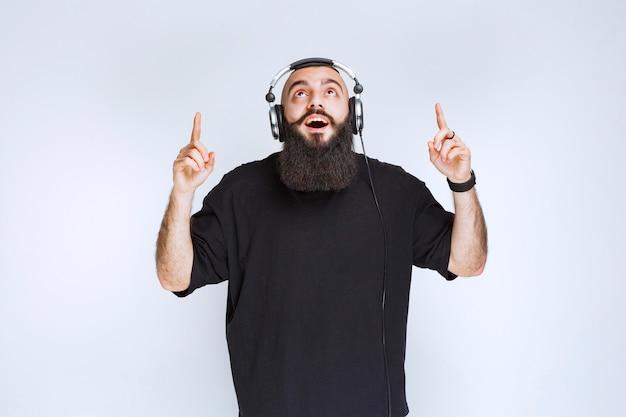 Dj con barba usando audífonos y apuntando hacia arriba.