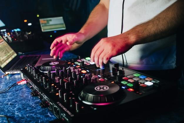Dj en una cabina tocando una mesa de mezclas en una discoteca