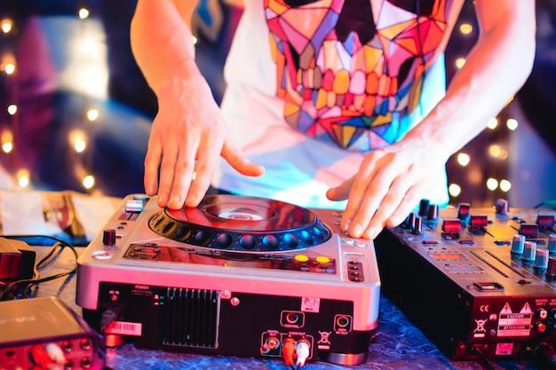 Dj en club nocturno trae música a la consola