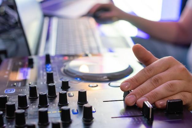 Dj controla un control remoto en una fiesta de club.