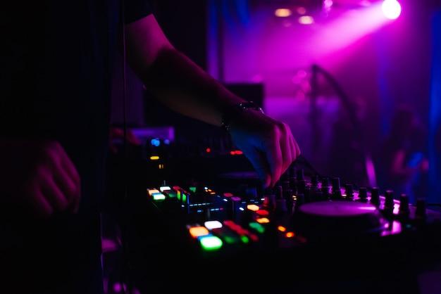 Dj controla la música en la discoteca moviendo los controladores en el tablero de música