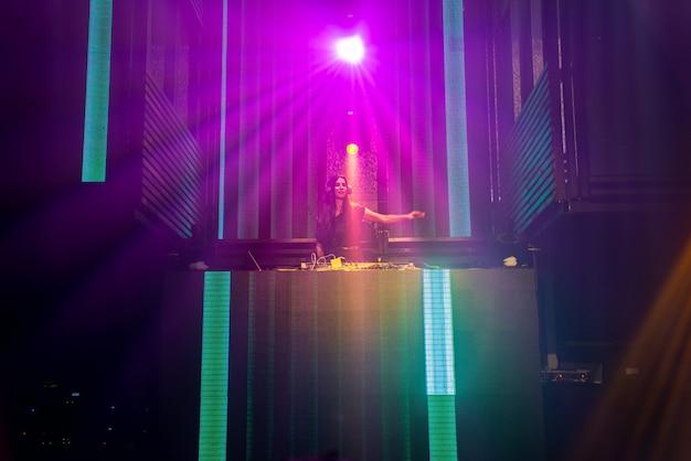 Dj en el escenario en la discoteca discoteca mezclando ritmo de música techno