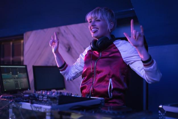 Dj femenina divirtiéndose mientras toca música en el bar