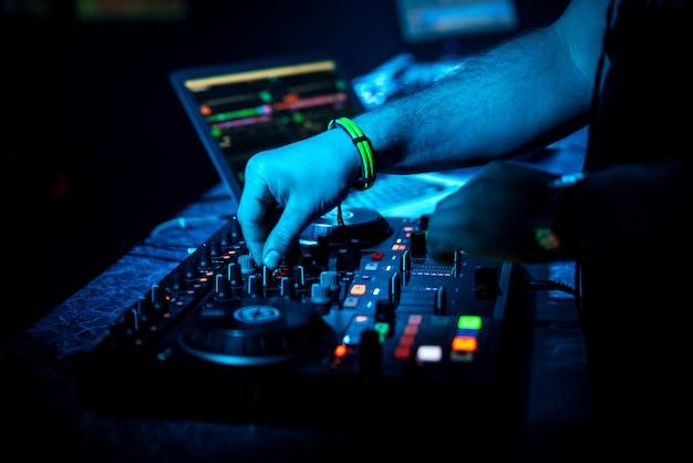 Dj de mano mezclando música en una placa controladora profesional