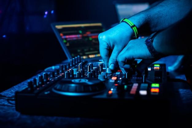 Dj de mano que mezcla música electrónica en un controlador profesional
