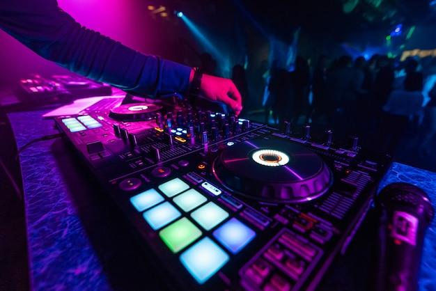 Dj mano toca un mezclador profesional en una discoteca