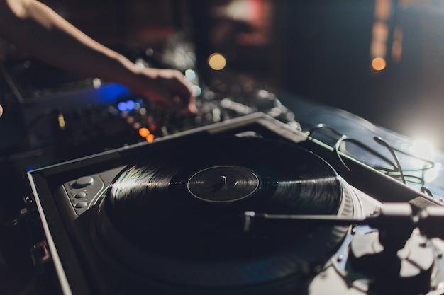 Dj manos en la cubierta del equipo y mezclador con disco de vinilo en la fiesta.