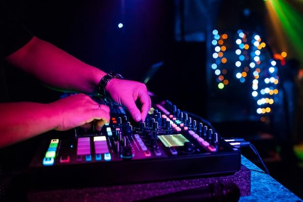Dj masculino mezcla música electrónica con sus manos en un mezclador de música profesional