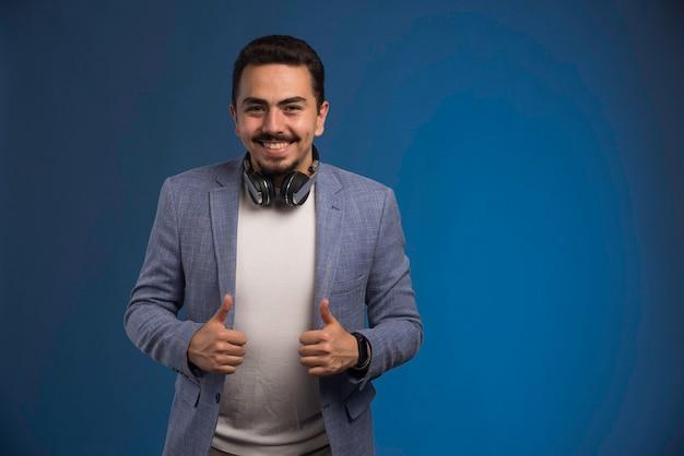 Dj masculino en traje gris con auriculares en el cuello.