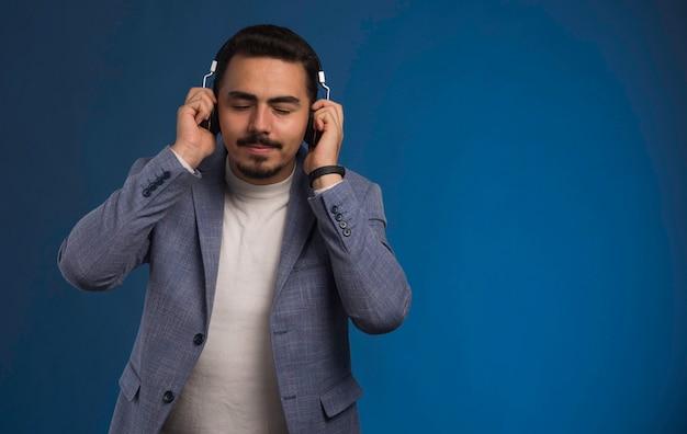 Dj masculino en traje gris escuchando auriculares y disfrutando.