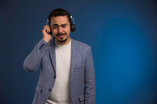 Dj masculino en traje gris escuchando auriculares y se toca.