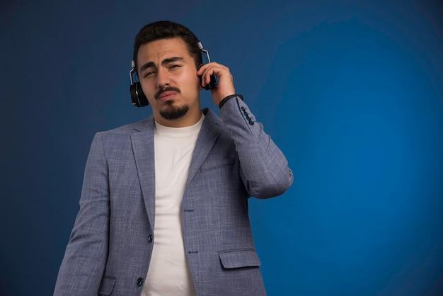 Dj masculino en traje gris escuchando auriculares.