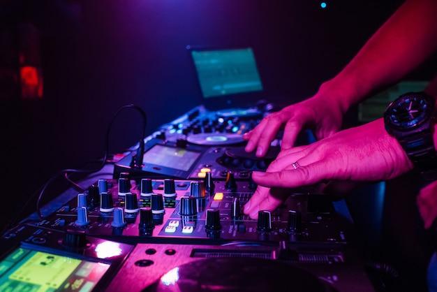 Dj mezcla a mano en una mesa de mezclas profesional en una discoteca