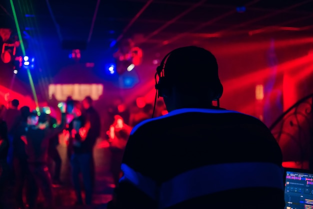 Dj mezcla música en una discoteca con gente bailando