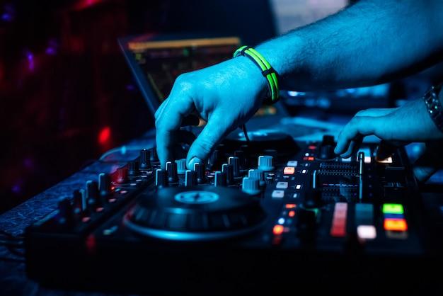Dj mezcla música electrónica en un controlador profesional en una discoteca