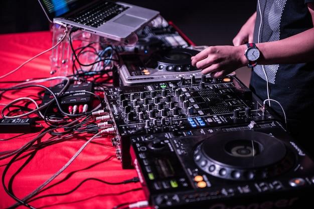 Dj mezcla la pista en el club nocturno en la fiesta, tocando la música en el plato en la fiesta