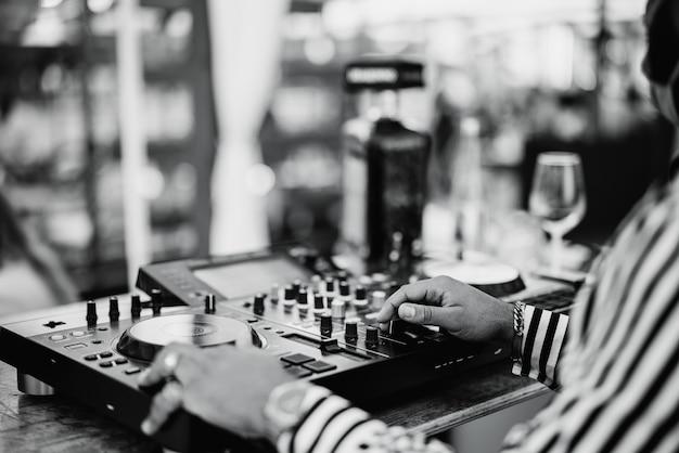Dj negro tocando música en el bar de cócteles al aire libre - concepto de entretenimiento y fiesta - enfoque en la mano derecha