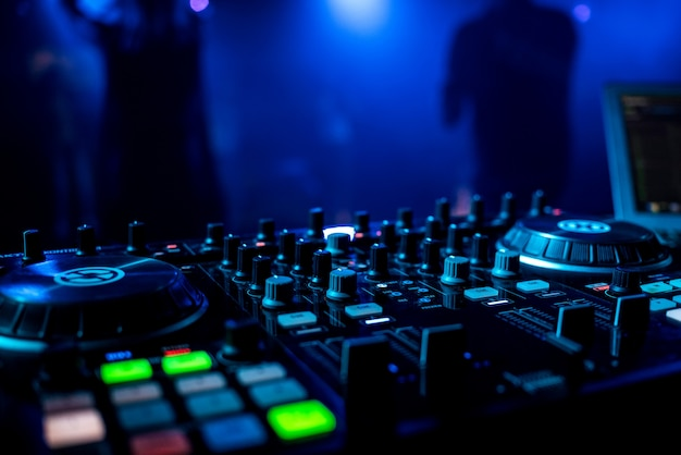 Dj profesional mezclador de música en una discoteca con botones
